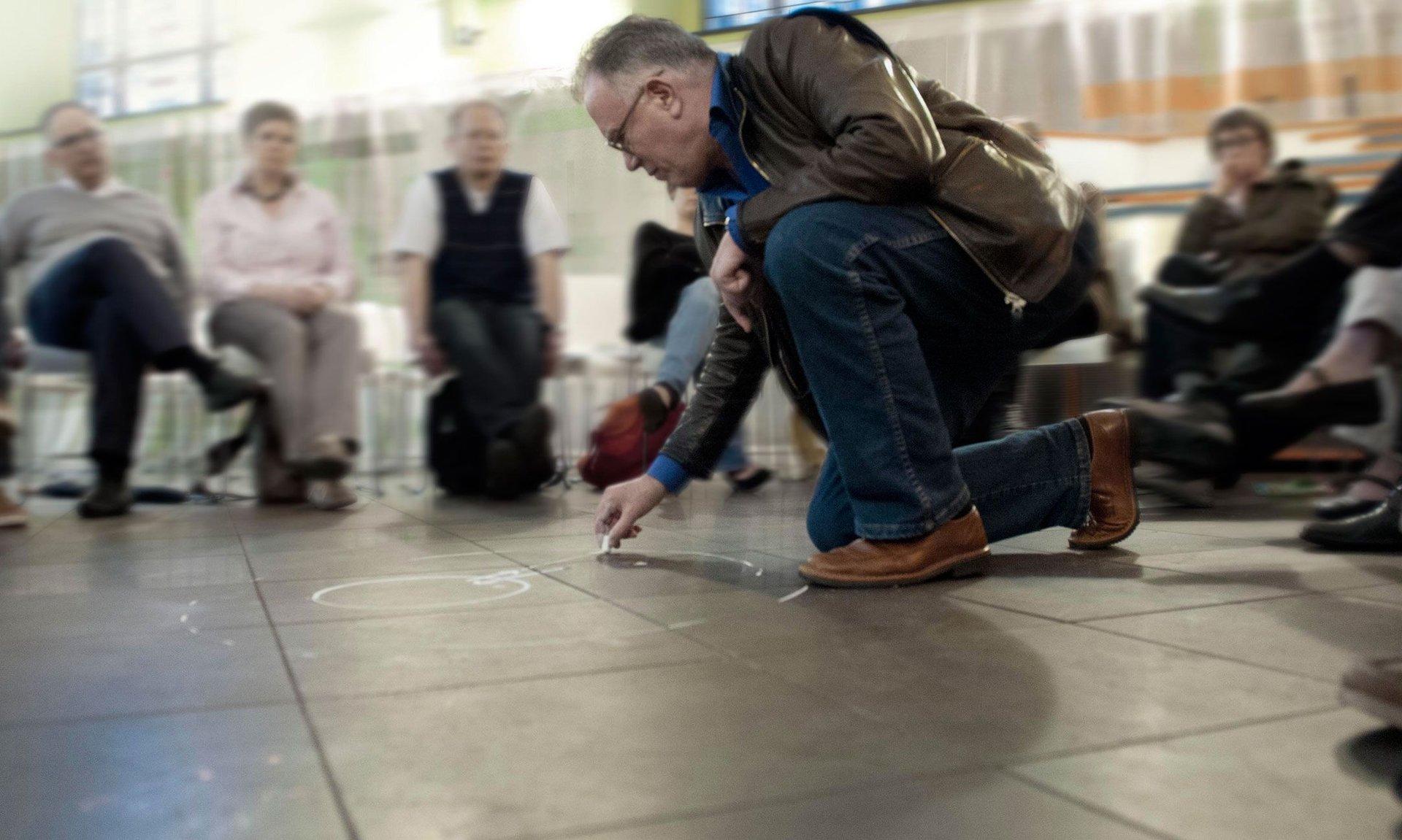 Johannes Stüttgen, der Leiter des Ringgesprächs, kniet im Stuhlkreis der Teilnehmer und zeichnet mit Kreide auf den Boden.