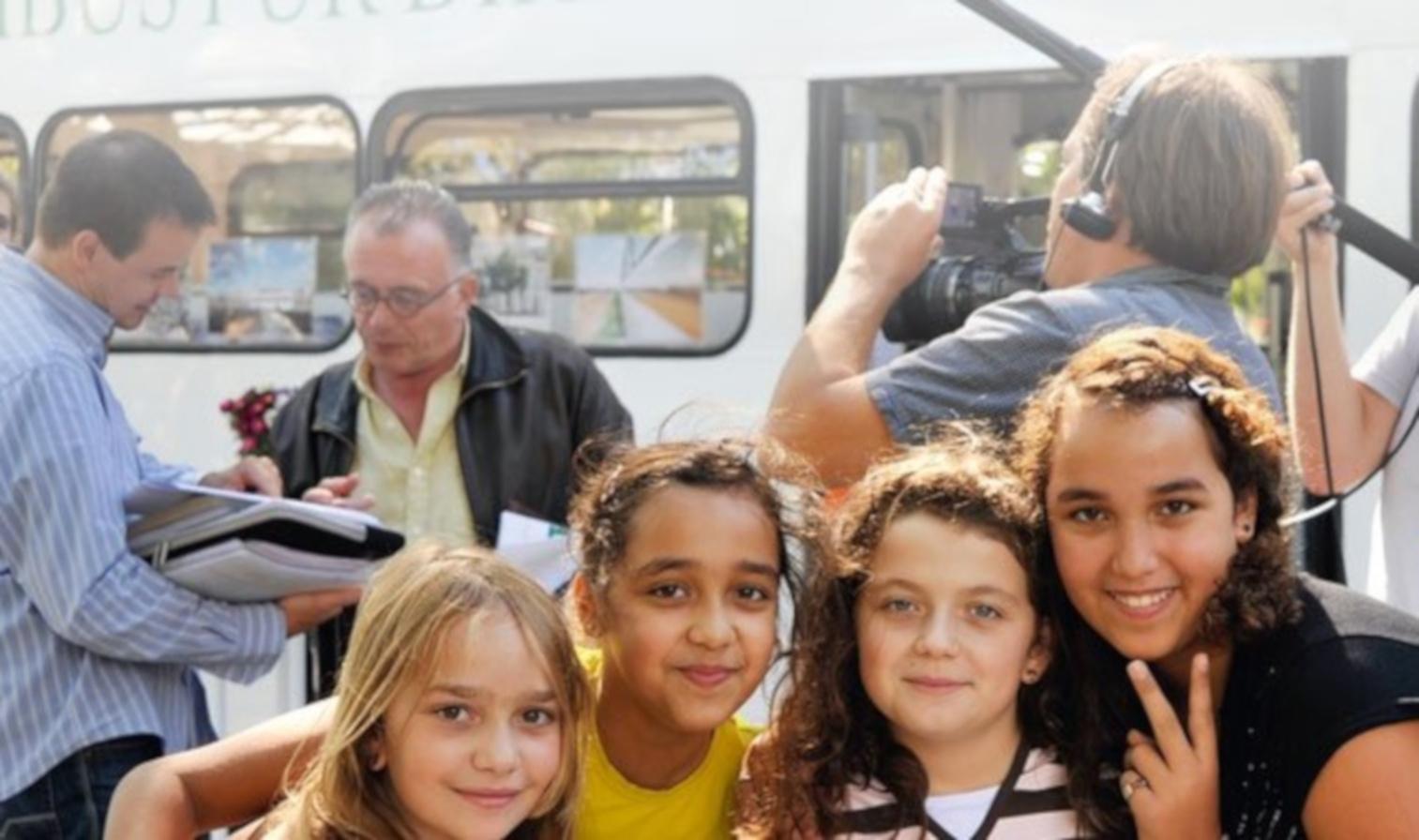 Mehrere Schüler und Mitarbeiter des Omnibus im Gespräch vor dem Omnibus